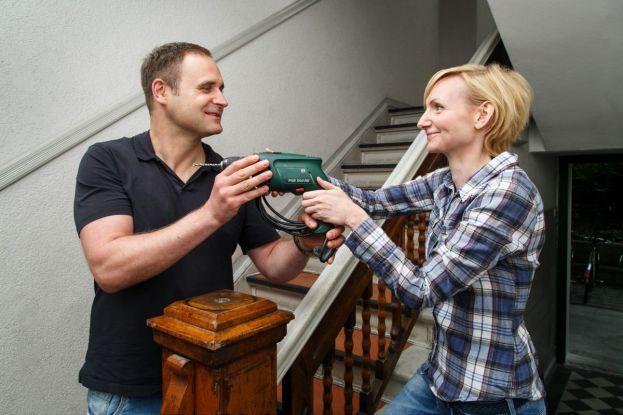 Ein Mann und eine Frau tauschen Werkzeug im Treppenhaus.