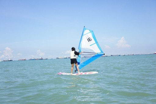 A participant tries windsurfing out in the open sea.
