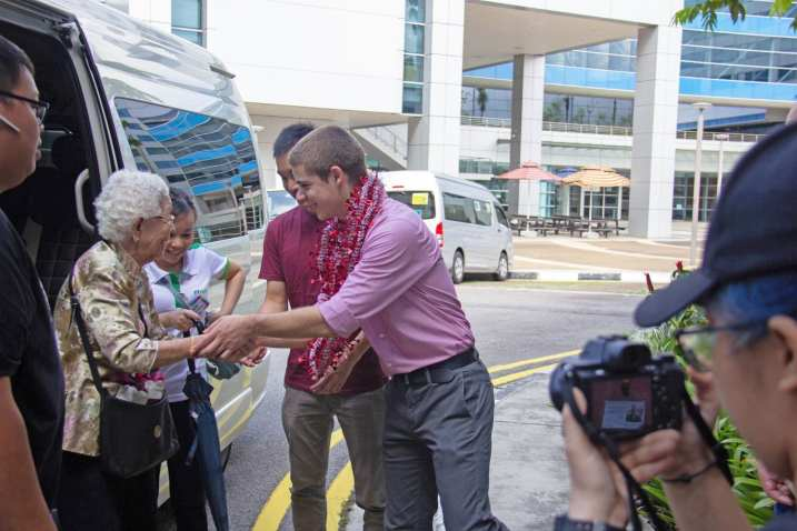 A volunteer welcoming an elderly partcipant to NTU.