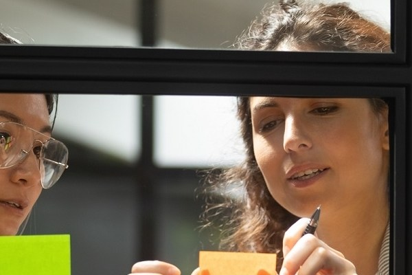 Two women using sticky notes to organize content