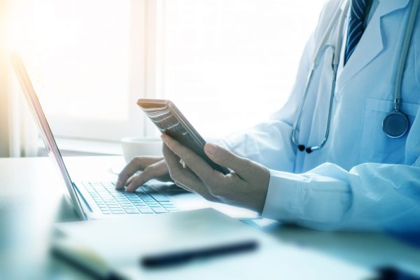 Doctor Using Smartphone In Office