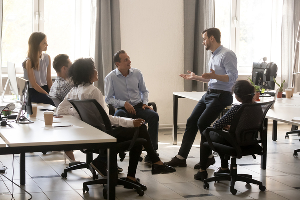 Male Team Leader Talking To Diverse Businesspeople At Office Meeting