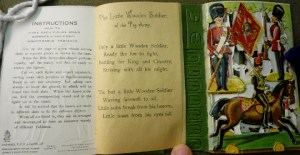 """Instructions"" on inside wrapper, the beginning of the poem, and the first leaf of toy soldiers folded-out (joined to green bases as shown here)."