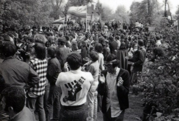 """A large group of people, some holding flags. In the foreground, a man is wearing a t-shirt with """"STRIKE"""" written over a closed fist on the back."""
