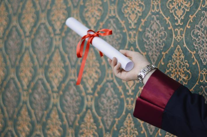 Person holding a diploma scroll