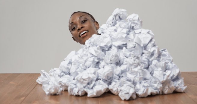 Person emerging from behind a stack of scrunches up paper