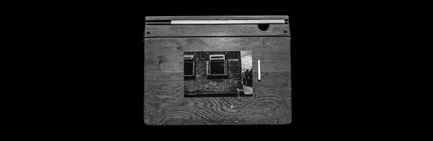 Still from 'Chalk Trace' b y Esther Johnson, courtesy of Esther Johnson, of a school desk and a photograph of windows of a building near to a chalk line