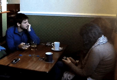An image of two people sat at the same table in a pub, both on their mobile phones