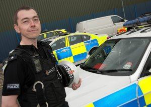 Adam Greenslade standing in front of police car