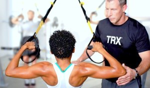 Personal trainers helps to workout with TRX Suspension Trainer