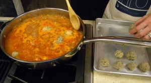 prawn albondigas (meatballs) are placed in the simmering sauce