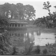 Black-and-white photo of an Imperial tomb on water surrounded by trees