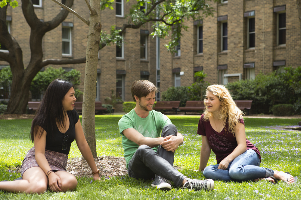 Three students sitting outside on the grass laughing
