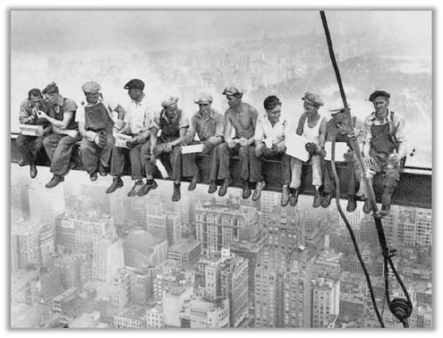 Men eating lunch atop a skyscraper they are building in New York City