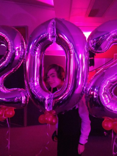 Rowan, smiling at camera,  dressed formally peeking through a 2020 balloon under purple light