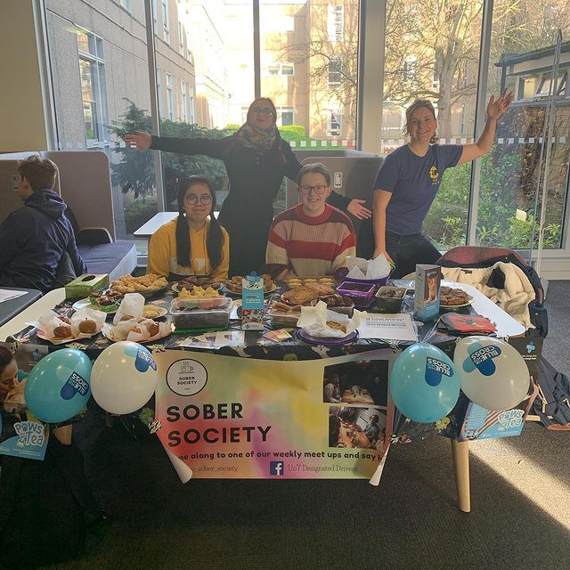 An Image of Amy (top left) and 3 other students sitting and standing around a table covered in baked goods. On the front of the table is a banner advertising Sober Society as well as balloons indicating they're raising money for the Blue Cross.