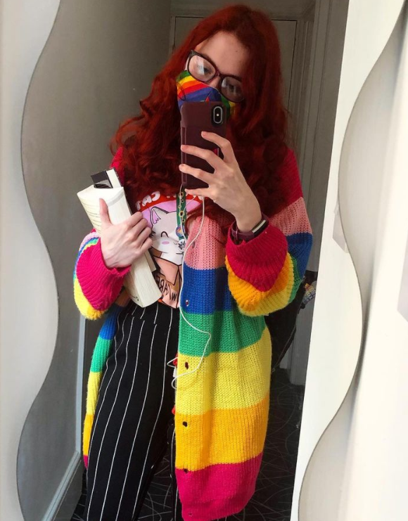 An image of Amy (white female) taking a selfie with my phone in a full-length mirror in a hall. Amy is wearing black and white striped trousers, a rainbow face mask and a rainbow cardigan, they are carrying some library books and you can see they are wearing a sunflower lanyard with some badges on it.