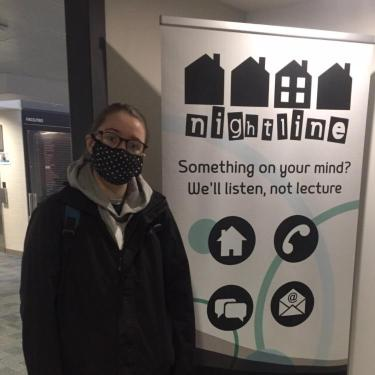 A female student wearing a face covering standing in front of a large 'Nightlint' poster.