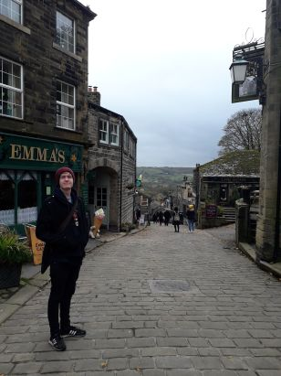 A student stood outside some shops on a cobbled street in Haworth