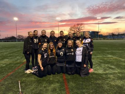 A group of female students dressed in sports kit - 8 students are standing and in front of them 5 students are kneeling. The sun is setting behind them and the sky is pink.