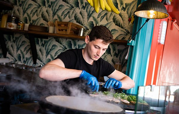 A man wearing a black tshirt and blue hygiene gloves cooking a crepe on a hotplate. A bunch of bananas is hanging above his head and there is a shelf behind his head.