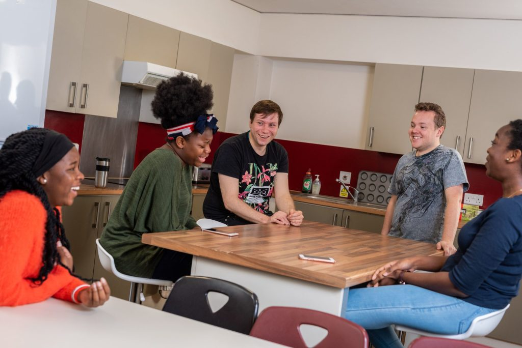 Students sitting around a kitchen island and laughing with their social circle.