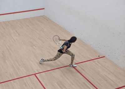A female student playing squash on an indoor squash court. She is lunging towards the ball about to take a shot.