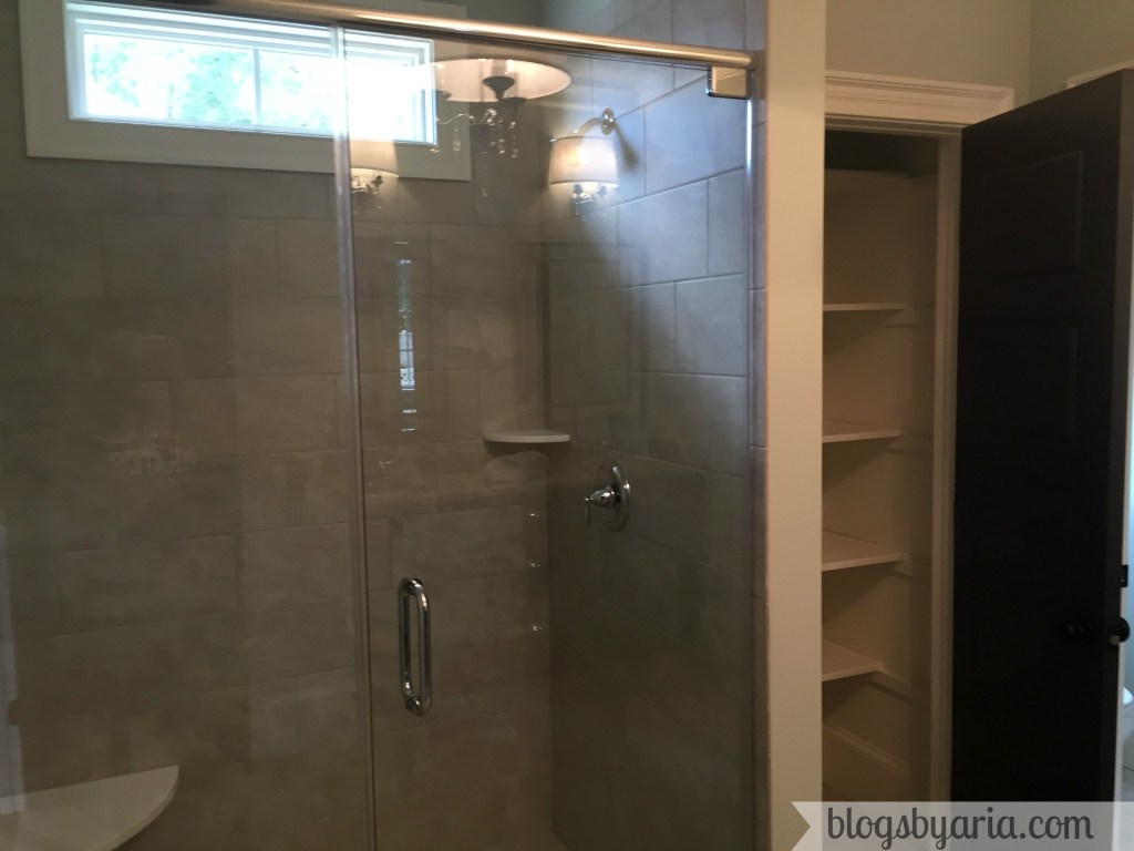 master bathroom shower with linen closet