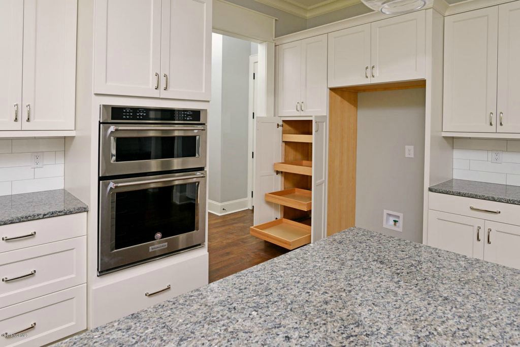 Off White kitchen with granite counters and built-in pantry with pull out shelves