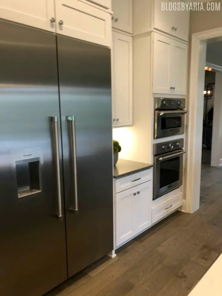 white kitchen wall fridge with double ovens and fridge