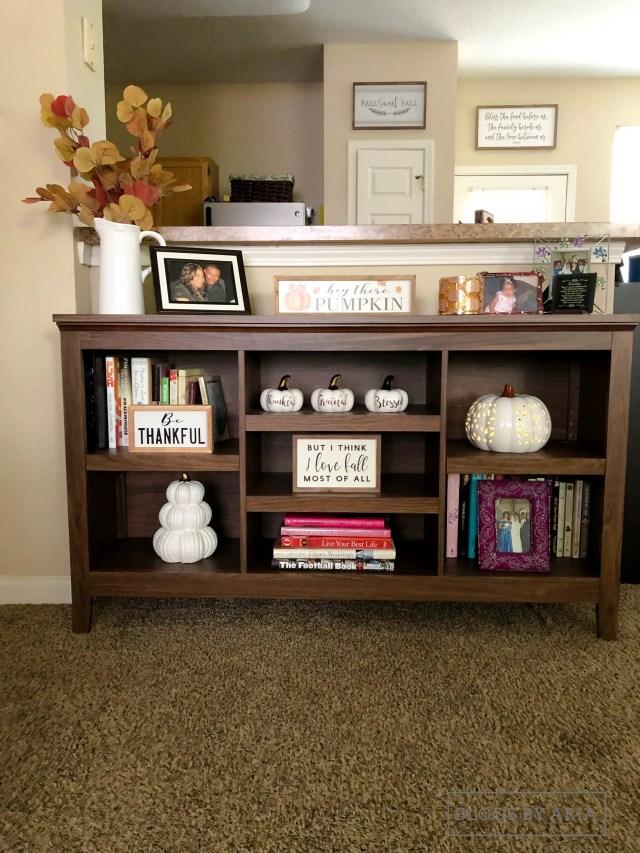 neutral pumpkins decorate this bookshelf for fall