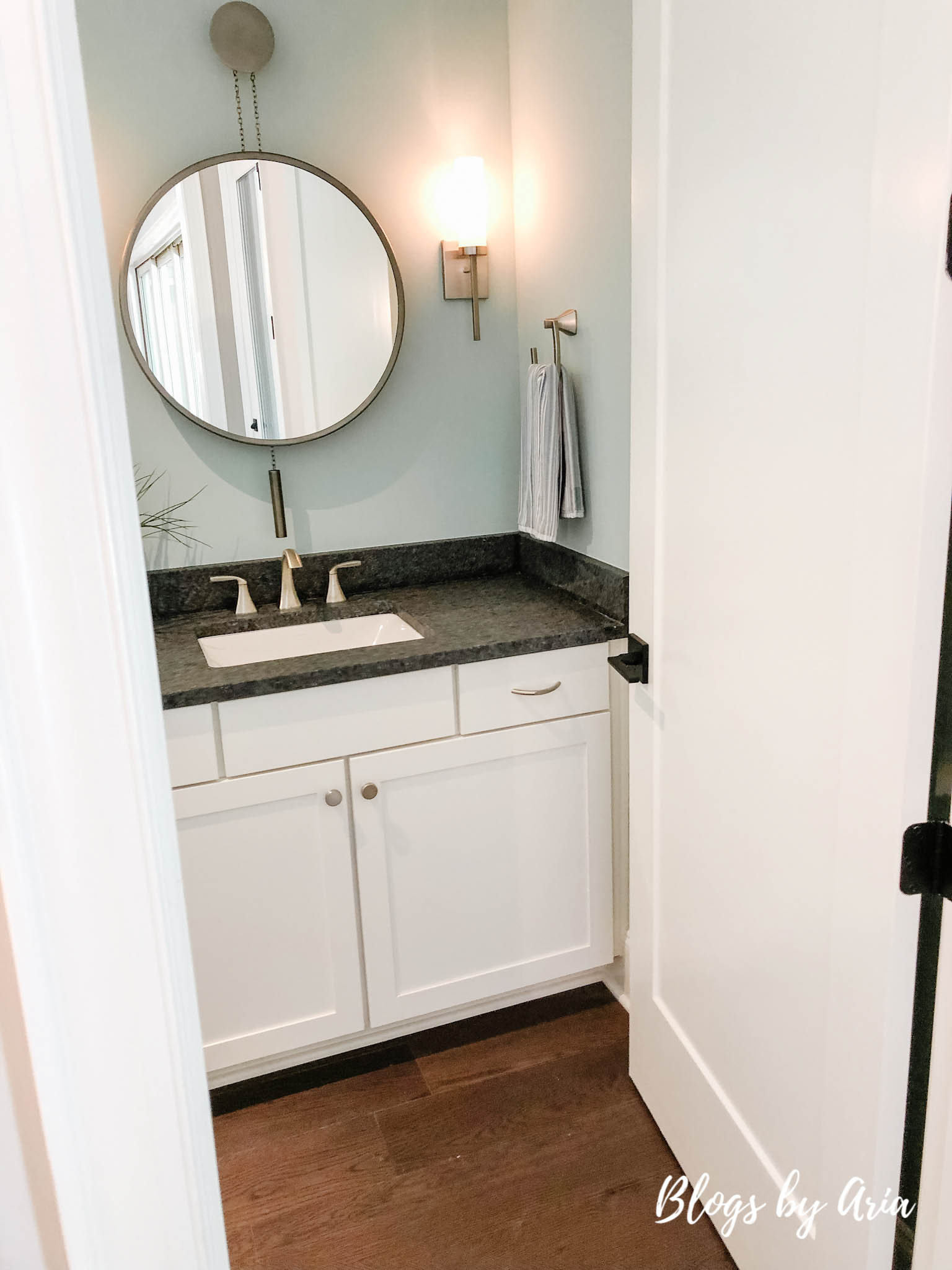 powder bathroom with round mirror