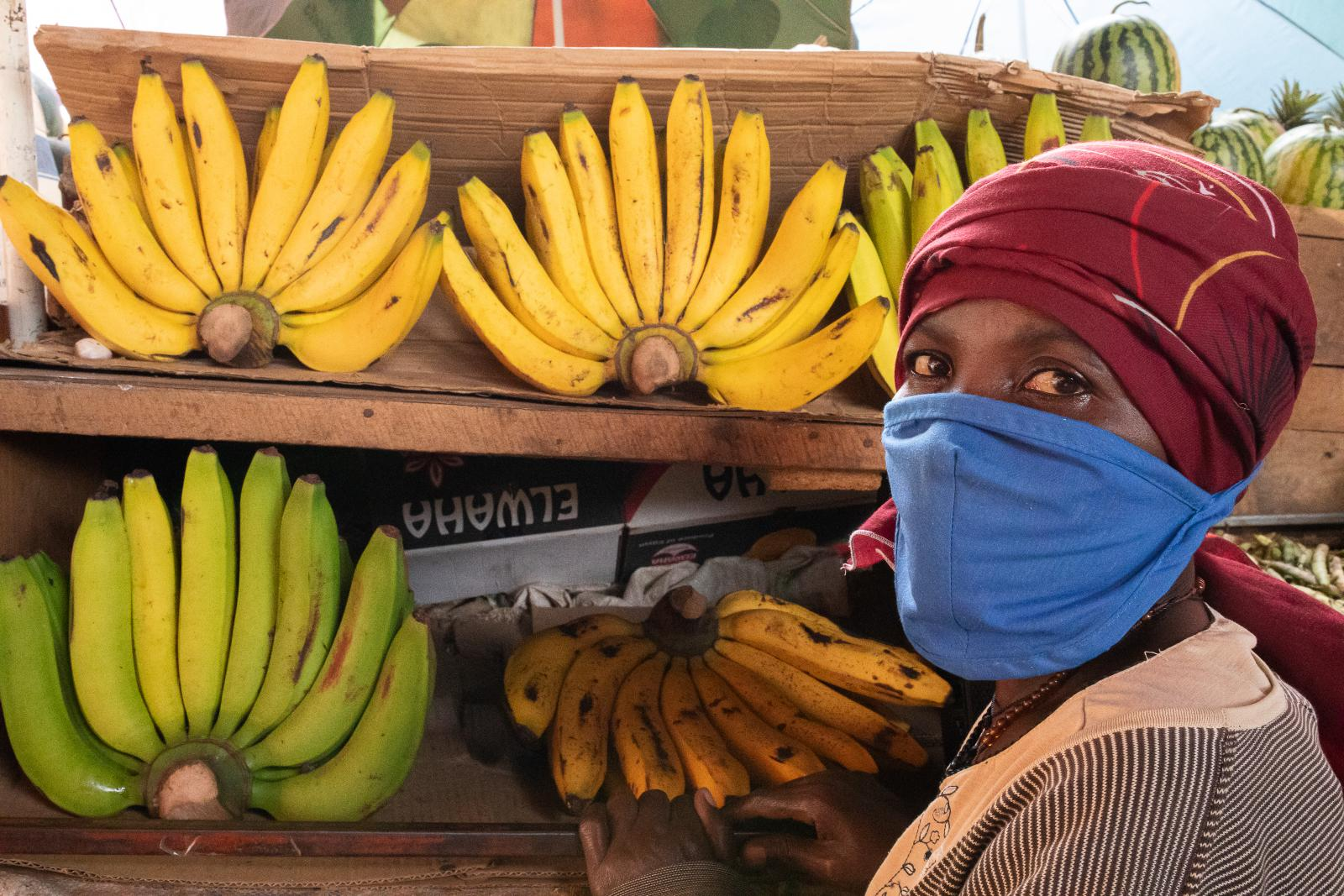 A woman in a face mask by fruit in Kampala