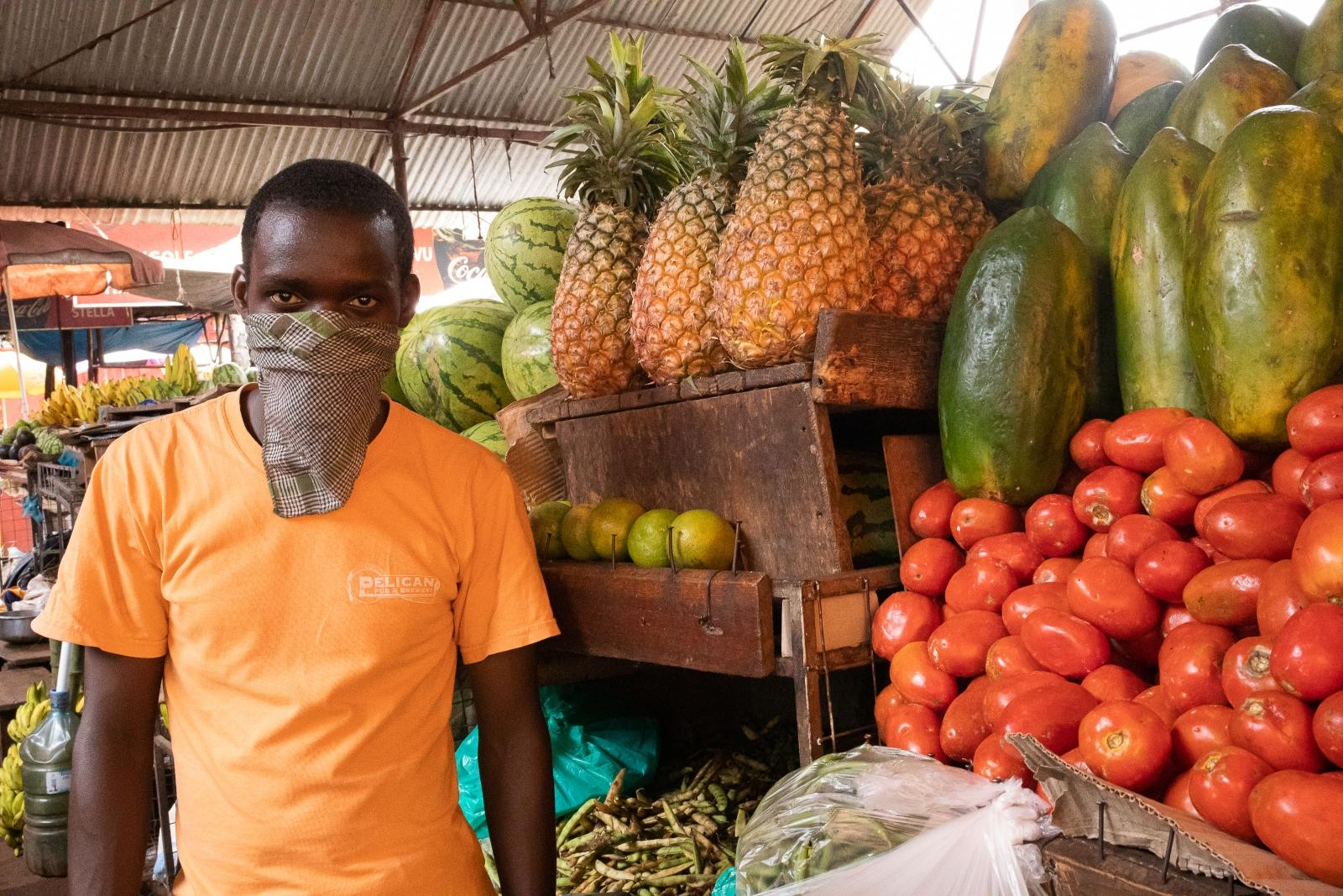 A man wearing a face mask by a market stall with fruit