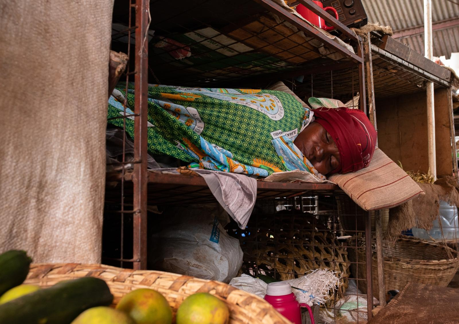 A woman asleep in her market stall on a ledge surrounded by fruit