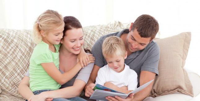 parents-et-enfants-en-train-de-lire-sur-le-divan