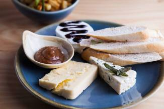 Cheese board with baguette, baked sweet apple and assorted cheese vessels. Photo: Judit Losh