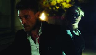 """Leo Barnes (FRANK GRILLO) leads Senator Roan (ELIZABETH MITCHELL) through dangerous territory in Universal Pictures' """"The Purge: Election Year"""" reveals the next terrifying chapter that occurs over 12 hours of annual lawlessness sanctioned by the New Founders of America to keep this country great."""