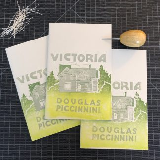 Three copies of Victoria by Douglas Piccinnini. The hand-printed linocut cover design consists of a gray house in a gradient green landscape, with gray title and author name lettering. The chapbooks are fanned out on a black gridded cutting mat, with a pile of string in the upper left, and a wooden-handled awl in the upper right.