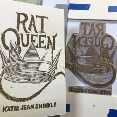 Linocut print cover of Rat Queen by Katie Jean Shinkle, printed in gold metallic ink on cream cardstock. To the right sits the linocut block, with the image—a large crown and rat tail descending from the Q in the title—in reverse.
