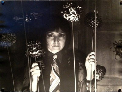 A black and white photo of Joyce Mansour, holding some glittery beaded decorations on sticks, and surrounded by more of same.