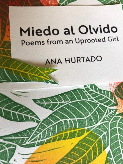 A closeup of the cover of Miedo al Olvido by Ana Hurtado, including multicolored ripe mangos and dark green leaves in a hand-printed linocut pattern, and text in black ink.