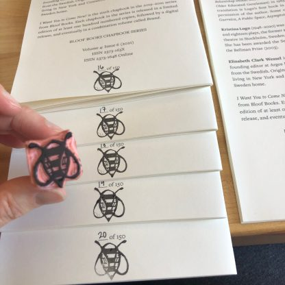 Several chapbook interiors are arranged in a fanned out stack, showing the colophon page. Each is numbered by hand and a linocut stamp of our logo bee has been applied at the bottom center. To the left, a woman's hand holds the stamp, carved in pink speedy-carve material and affixed to a wine cork handle.