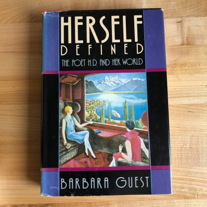 A copy of Herself Defined in hardcover, wrapped in a multicolored color-blocked jacket in purple and black with a central painting of two women looking out a window over a landscape with water.