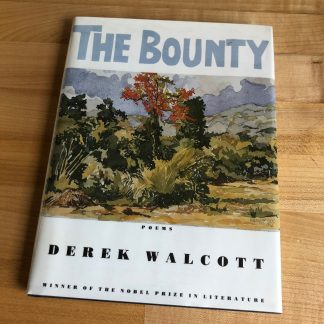 The Bounty by Derek Walcott in hardcover, lying on a maple tabletop. The white jacket features a multicolored painting in the center, with light blue-gray title lettering above and the author's name below in black.
