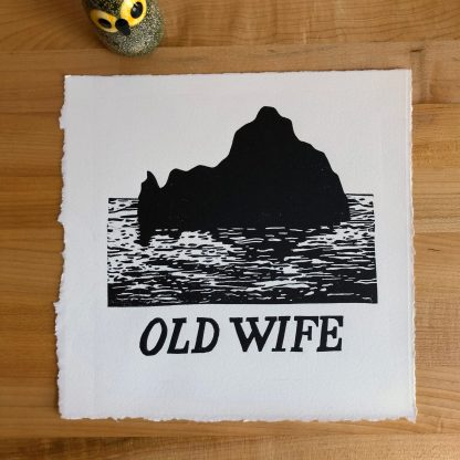 Old Wife print in 9 x 9 size depicting a silhouetted small island and water in graphic black on textured natural white paper, lying on a maple tabletop. The edges are a combination of natural deckle and ruled torn. A small ceramic owl figurine sits next to the print in the upper left.