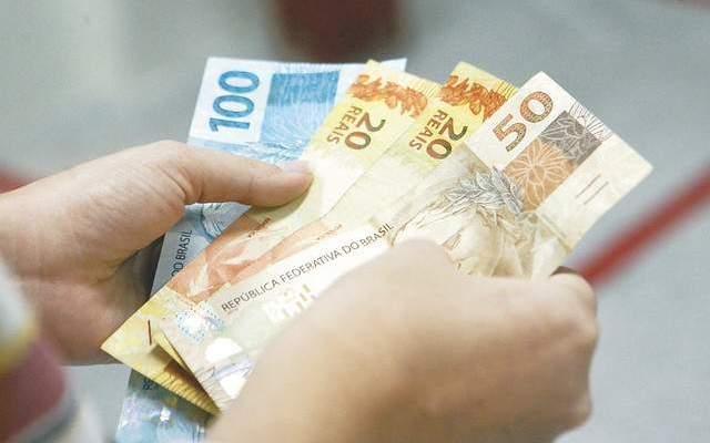 mao contando o dinheiro do auxilio cidadão emergencial