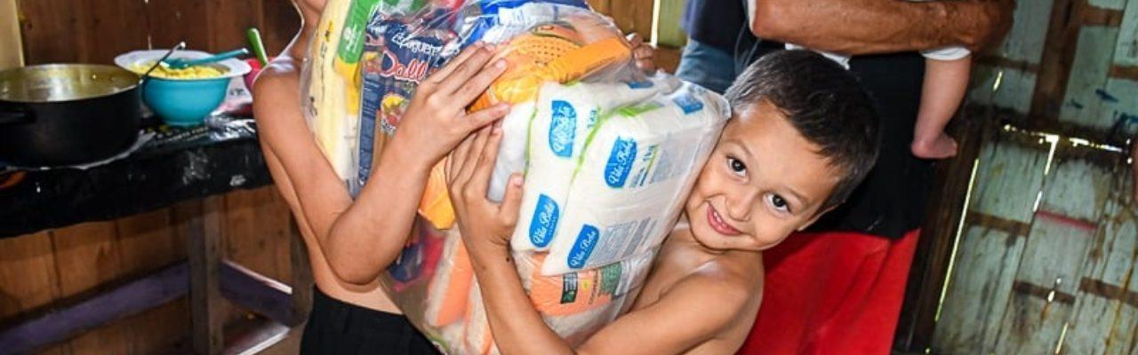 dois irmão carregando uma cesta básica