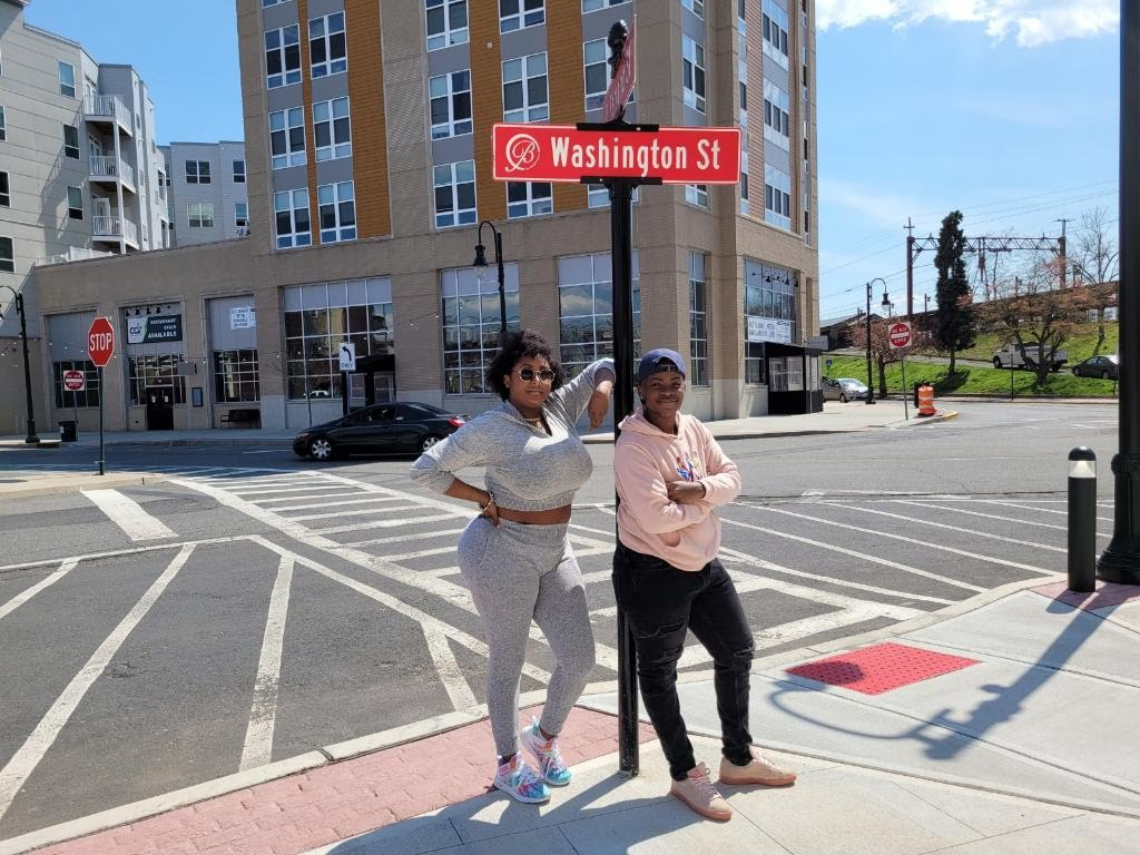 Medina Wingo and Diamond Wyche stand in front of a street sign that says Washington St.