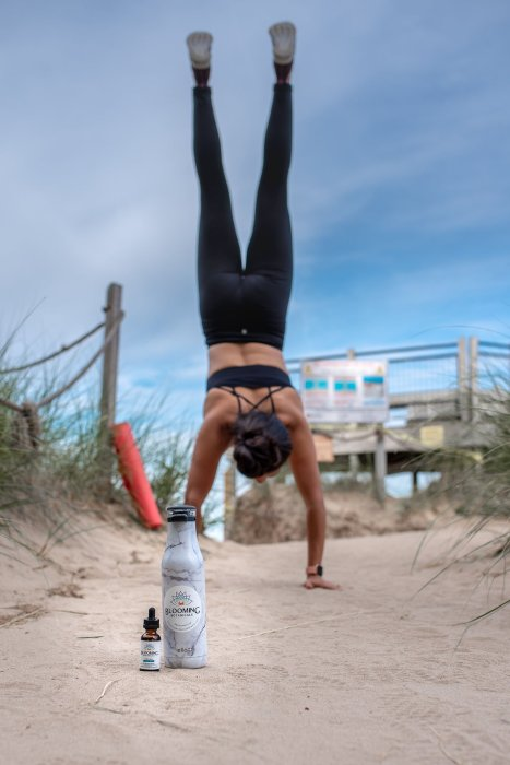 A woman with her hands on the ground and legs in the air next to a Blooming Botanicals CBD tincture